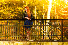 Beauty girl relaxing in autumn park with bicycle, outdoor Royalty Free Stock Photos