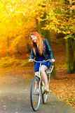 Beauty girl relaxing in autumn park with bicycle, outdoor Stock Image