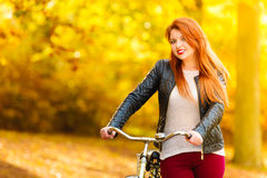 Beauty girl relaxing in autumn park with bicycle, outdoor Royalty Free Stock Image