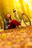 Beauty girl relaxing in autumn park with bicycle, outdoor Royalty Free Stock Photography
