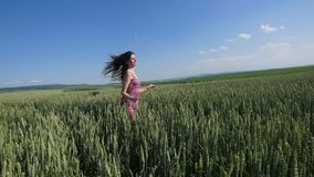 Beauty girl running on green wheat field. Freedom concept. Happy woman outdoors Royalty Free Stock Photography
