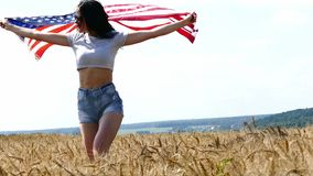 Beauty Girl Running On Yellow Wheat Field with US national flag. Happy Woman Outdoors. Harvest stock video footage