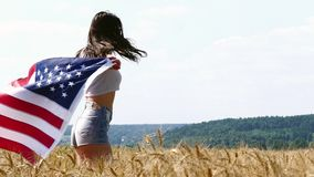 Beauty Girl Running On Yellow Wheat Field with US national flag. Happy Woman Outdoors. Harvest stock footage
