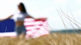 Beauty Girl Running On Yellow Wheat Field with US national flag. Happy Woman Outdoors. Harvest stock video