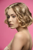 Beauty girl with short curly hair. Sensual blonde girl posing in beauty shoot with healthy short curly hair, natural make-up and naked shoulders Royalty Free Stock Image