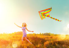 Beauty girl in short dress running with flying colorful kite Royalty Free Stock Images