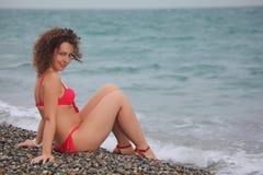 Beauty girl sits on pebble beach Royalty Free Stock Photos