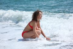 Beauty girl sits in sea surf Royalty Free Stock Photo