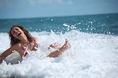 Beauty girl sits in sea surf Stock Photo