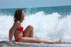 Beauty girl sits in sea surf Stock Image