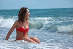 Beauty girl sits in sea surf Royalty Free Stock Image