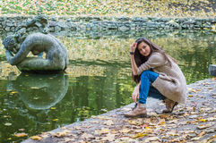 Beauty girl sitting near the pond Royalty Free Stock Image