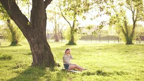 Beauty Girl sitting under the tree stock video