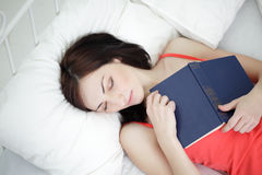 Girl slip with book Stock Images