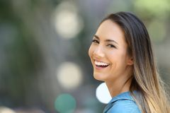 Beauty girl smiling with perfect teeth on the street. Beauty girl smiling with perfect teeth and looking at camera on the street royalty free stock image