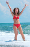 Beauty girl stands in sea surf with rised hands Royalty Free Stock Photos