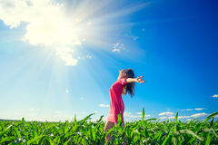 Beauty girl on summer field rising hands over blue clear sky. Happy young healthy woman enjoying nature outdoors Royalty Free Stock Image