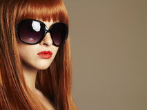 Beauty Girl in sunglasses. Healthy Red Hair. Beautiful Young Woman with red lips. Beauty Girl in sunglasses. Healthy Red Hair. Beautiful Young Woman in Stock Image