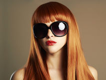 Beauty Girl in sunglasses. Healthy Red Hair. Beautiful Young Woman with red lips Stock Image
