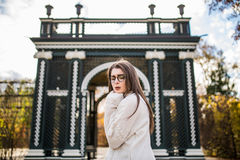 Beauty girl in sweater and glasses posing in autumn garden of castle Royalty Free Stock Photo