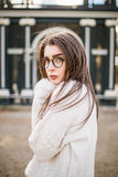 Beauty girl in sweater and glasses posing in autumn garden of castle Stock Photos