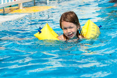 Beauty girl in swimming pool. Beauty girl with armlet is swimming in swimming pool with blue water stock photo
