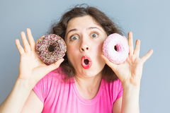 Beauty girl taking colorful donuts. Funny joyful woman with sweets, dessert. Diet, dieting concept. Junk food Stock Photos