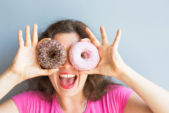 Beauty girl taking colorful donuts. Funny joyful woman with sweets, dessert. Diet, dieting concept. Junk food Royalty Free Stock Images