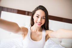 Beauty girl taking selfie from phone in the morning in bed at home. Beauty girl taking selfie from phone in the morning in bed Royalty Free Stock Image