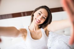 Beauty girl taking selfie from phone in the morning in bed at home. Beauty girl taking selfie from phone in the morning in bed Royalty Free Stock Photos