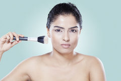 Beauty girl using makeup brush Stock Photos