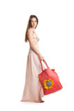 Beauty girl walk in rose dress and red beach bag Royalty Free Stock Images