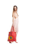 Beauty girl walk in rose dress and red beach bag Royalty Free Stock Photos
