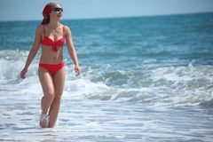 Beauty girl walk in sea surf. Summer Stock Images
