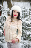 Beauty girl in warm woolen sweater under snow-covered trees Royalty Free Stock Photo