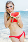 Beauty girl is wearing red swimsuit eating Stock Photos