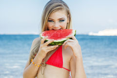 Beauty girl is wearing swimsuit eating watermelon Royalty Free Stock Image