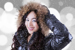 Beauty girl in winter clothing. Young pretty girl smiling on the camera while wearing a winter fur jacket with light glitter background Stock Images