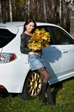 Beauty girl with yellow leaves and white car Stock Photo