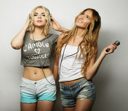 Beauty girls with a microphone singing and dancing Stock Images