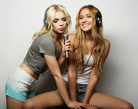 Beauty girls with a microphone singing and dancing. Life style, happiness, emotional and people concept: beauty hipster girls with a microphone singing and Royalty Free Stock Photography