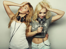 Beauty girls with a microphone singing and dancing. Life style, happiness, emotional and people concept: beauty hipster girls with a microphone singing and Stock Photos