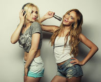 Beauty girls with a microphone singing and dancing. Life style, happiness, emotional and people concept: beauty hipster girls with a microphone singing and Stock Photography