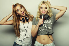 Beauty girls with a microphone singing and dancing. Life style, happiness, emotional and people concept: beauty hipster girls with a microphone singing and Stock Images