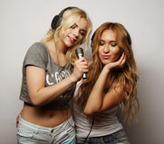 Beauty girls with a microphone singing and dancing. Life style, happiness, emotional and people concept: beauty hipster girls with a microphone singing and Royalty Free Stock Photos