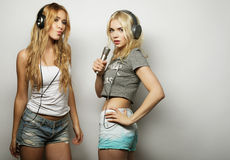 Beauty girls with a microphone singing and dancing Stock Photos