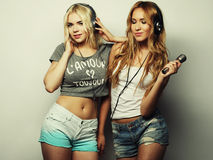 Beauty girls with a microphone singing and dancing Royalty Free Stock Photography
