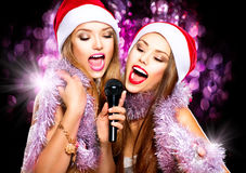 Beauty girls in santa hats singing Stock Photos