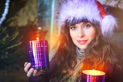 Beauty glamor Woman celebrating christmas, wearing a carnival cap. Party, festive New Year`s background with a Christmas tree fire and mittens. Celebrating Royalty Free Stock Images