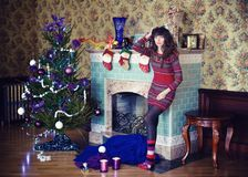 Beauty glamor Woman celebrating Christmas wearing a dress, festive Christmas background with the fire of a Christmas tree and mitt Royalty Free Stock Photos